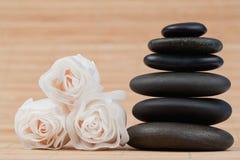 Fermez-vous vers le haut des roses et d'une pile noire de cailloux Photos stock