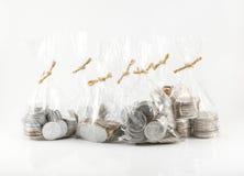 Fermez-vous vers le haut des sacs des pièces de monnaie sur le fond blanc pour financier et le sav Photo libre de droits
