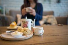 Fermez-vous vers le haut des scones avec du beurre et le thé sur la table Photos libres de droits