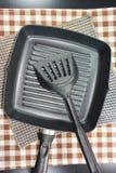 Fermez-vous vers le haut des ustensiles de poêle et de cuisine sur la table Photo stock