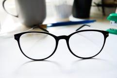 Fermez-vous vers le haut des verres noirs d'affaires sur le blanc Photographie stock libre de droits