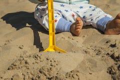 Fermez-vous vers le haut du bébé garçon jouant avec des jouets de sable à la plage Photos stock