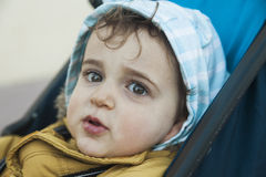 Fermez-vous vers le haut du bébé garçon mignon de portrait regardant l'appareil-photo avec grand g Photographie stock libre de droits