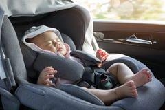 Fermez-vous vers le haut du bébé nouveau-né mignon asiatique dormant dans le siège de voiture moderne Photos stock