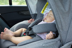 Fermez-vous vers le haut du bébé nouveau-né mignon asiatique dormant dans le siège de voiture moderne Image libre de droits