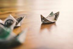 Fermez-vous vers le haut du bateau du dollar sur le concept en bois de chef de table Photographie stock libre de droits