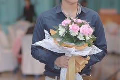 Fermez-vous vers le haut du beau bouquet de la fleur pour son amie avec le jeune homme asiatique beau Jour du ` s de valentine ou Photographie stock libre de droits
