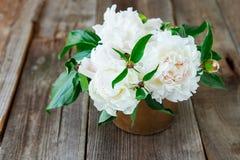 Fermez-vous vers le haut du bouquet frais des pivoines blanches dans la cuvette de vintage sur le vieux fond rustique en bois Jus Photographie stock libre de droits