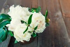 Fermez-vous vers le haut du bouquet frais des pivoines blanches dans la cuvette de vintage sur vieux W Photo stock