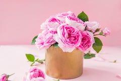 Fermez-vous vers le haut du bouquet tendre de roses de thé rose dans le pot d'or de vintage sur le fond rose Moquerie de carte po Images stock
