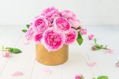 Fermez-vous vers le haut du bouquet tendre de roses de thé rose dans le pot d'or de vintage sur la table en bois blanche Fond flo Photographie stock