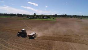 Fermez-vous vers le haut du bourdon tiré d'un tracteur semant un champ au printemps banque de vidéos