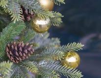 Fermez-vous vers le haut du cône de pin et des boules d'or de Noël sur artificiel Photo stock