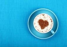 Fermez-vous vers le haut du café de cappuccino de latte dans la tasse sur le bleu Photographie stock