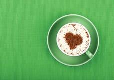 Fermez-vous vers le haut du café de cappuccino de latte dans la tasse sur le vert Photo stock