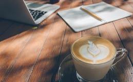 Fermez-vous vers le haut du carnet et de l'ordinateur portable de fond d'art de latte de café sur le ton en bois de vintage de ta Photos stock