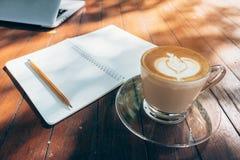 Fermez-vous vers le haut du carnet et de l'ordinateur portable de fond d'art de latte de café sur le ton en bois de vintage de ta Image stock