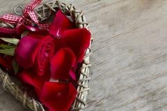Fermez-vous vers le haut du coeur en bois avec Rose et des pétales Photographie stock libre de droits
