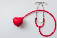 Fermez-vous vers le haut du coeur et du stéthoscope rouges sur le fond blanc Photo libre de droits