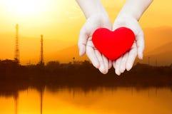 Fermez-vous vers le haut du coeur rouge chez des mains de la femme, d'isolement sur le fond de paysage d'énergie d'industrie, san Photographie stock libre de droits
