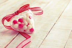 Fermez-vous vers le haut du coeur transparent avec des pilules de sucrerie, jour du ` s de valentine Photos libres de droits