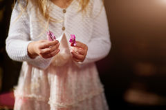 Fermez-vous vers le haut du détail des mains du ` s de fille d'enfant en bas âge jouant avec une petite fleur Image libre de droits