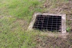 Fermez-vous vers le haut du drain de gril de l'égout autour de la rue ou du passage couvert photographie stock