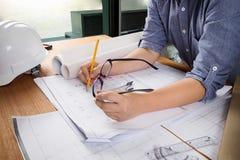 Fermez-vous vers le haut du fonctionnement de l'homme de l'architecte esquissant un proje de construction Image libre de droits