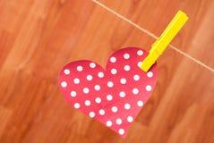 Fermez-vous vers le haut du foyer rouge avec les points de polka et la pince à linge jaune accrochés sur la corde de chanvre sur  Image libre de droits
