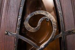 Fermez-vous vers le haut du fragment du modèle en métal sur la porte en bois Photographie stock libre de droits