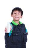 Fermez-vous vers le haut du garçon souriant et montrant la bouteille de lait, sur le blanc Photographie stock libre de droits