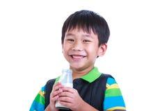Fermez-vous vers le haut du garçon souriant et tenant la bouteille de lait, sur le blanc Photo libre de droits