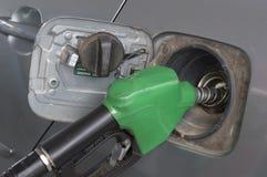 Fermez-vous vers le haut du gicleur d'essence vert. et voiture à la station service Image stock