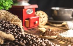 Fermez-vous vers le haut du grain de café sur le morcellement de café sous la cuillère photo stock