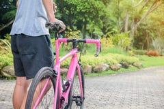 Fermez-vous vers le haut du hippie sur le vélo en parc au coucher du soleil Tiré avec le sunflare et sans visage photo libre de droits