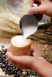 Fermez-vous vers le haut du lait se renversant dans le latte chaud à café - foyer mou images stock