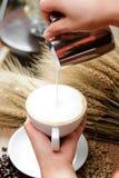 Fermez-vous vers le haut du lait se renversant dans le latte chaud à café - foyer mou images libres de droits