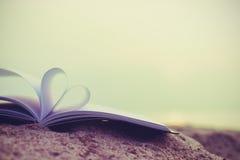 Fermez-vous vers le haut du livre de coeur sur le sable dans la plage avec le fond de tache floue de filtre de vintage Photographie stock