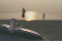 Fermez-vous vers le haut du livre de coeur sur le sable dans la plage avec le fond de tache floue de filtre de vintage Image libre de droits