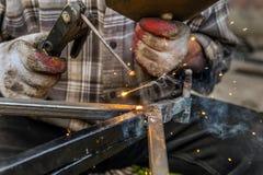 Fermez-vous vers le haut du macro de la soudure dans l'atelier, soudeuse masculine à l'aide de l'électrode Photos stock