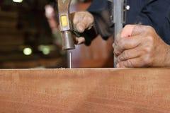 Fermez-vous vers le haut du marteau et du clou en employant par le charpentier sur le conseil en bois Centre sélectif et profonde Images libres de droits