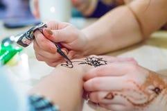 Fermez-vous vers le haut du mehendi femelle de peinture de mains en main photo libre de droits