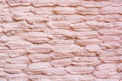Fermez-vous vers le haut du mur en pierre couvert de vieux plâtre rose Images stock