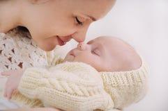 Fermez-vous vers le haut du nez émouvant du visage de la mère par le nez de son bébé Photographie stock libre de droits