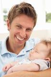 Fermez-vous vers le haut du père caressant le bébé nouveau-né chez Ho Images stock