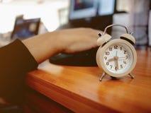 Fermez-vous vers le haut du petit réveil avec la main de dirigeant sur l'ordinateur portable photographie stock libre de droits