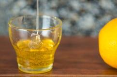 Fermez-vous vers le haut du petit verre se reposant sur le bureau en bois avec du miel tombant dans lui d'en haut, citron du côté Photographie stock libre de droits