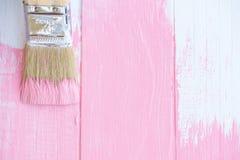 Fermez-vous vers le haut du pinceau peignant la couleur rose sur une table en bois blanche photographie stock