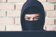 Fermez-vous vers le haut du pirate informatique de visage travaillant sur son ordinateur, pirate informatique volant la PA image libre de droits