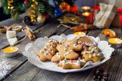 Fermez-vous vers le haut du plat avec les biscuits faits maison de pain d'épice sur la vieille table en bois rustique avec des bo Photos libres de droits